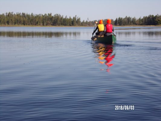 Natalie Bradshaw photo taken on the lake of two students in a canoe.
