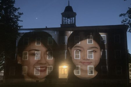 image of faces projected on building