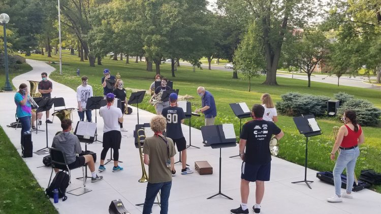 Professor Joe Dieker rehearses the Brass Ensemble outdoors, according to pandemic guidelines including special masks, distancing, and limited time.