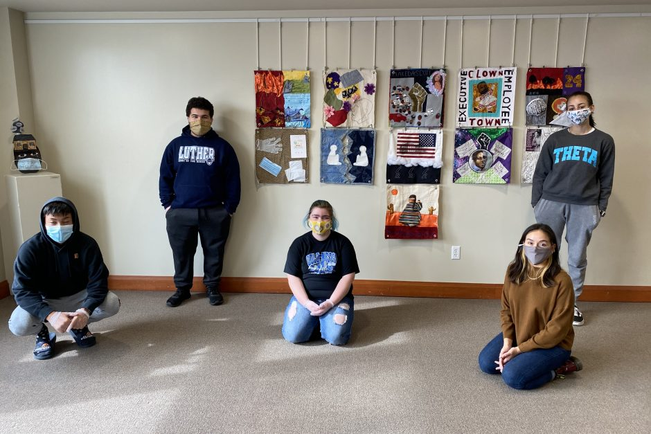 Students with their artistic creations behind them