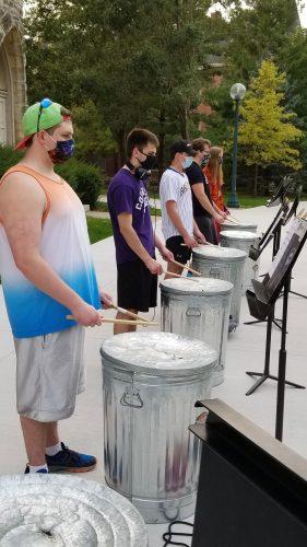 A percussion ensemble rehearses outdoors.