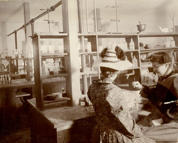 Two women conduct an experiment in a coed Cornell College chemistry laboratory in 1898 (note the men visible behind them). The woman at right is wearing an apron and oversleeves.