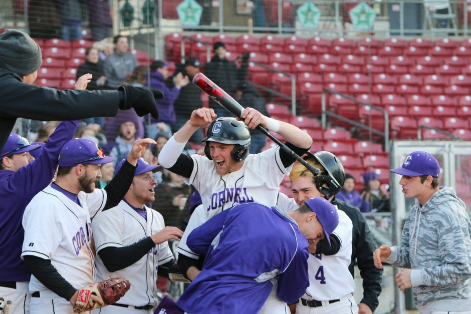 Teammates congratulate team captain Lucas Larson '19 after scoring a run against rival Coe College in 2018.