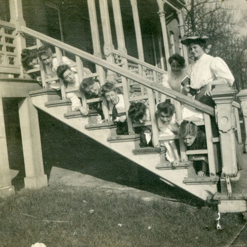 Bowman Hall residents have a little old-fashioned fun on the front porch steps in this undated archival photo.