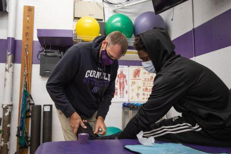 Head Athletic Trainer Loren Nydegger treats football player Demarius Pittman '22 in the training room. Photo by Ray Borchert '24.