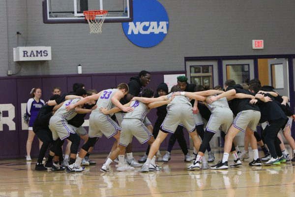 Daniel Burford '22 (center left inside circle) leads his teammates in a ritual to build spirit prior to a 2020 men's basketball game in the Small Sport Center.
