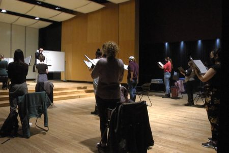 Choir members rehearse for the May 2 concert.