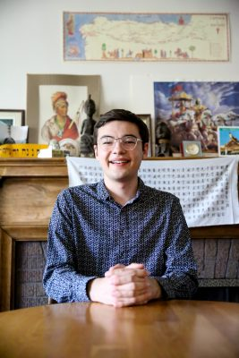 Alex Nelson sits inside Prall House on Cornell's campus.