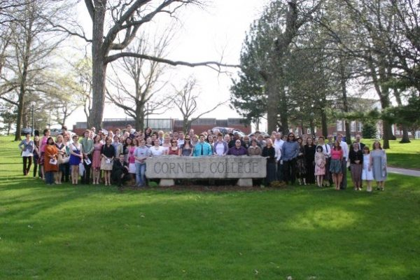 People standing behind the Cornell sign