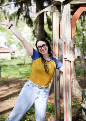 Jenna Makkawy, Class of 2021, stands near the swinging bench by Hanson House.
