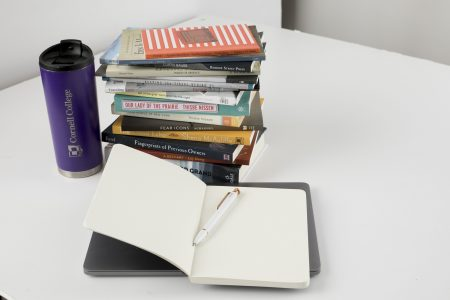 Bookes stacked up, open notebook, and Cornell College mug