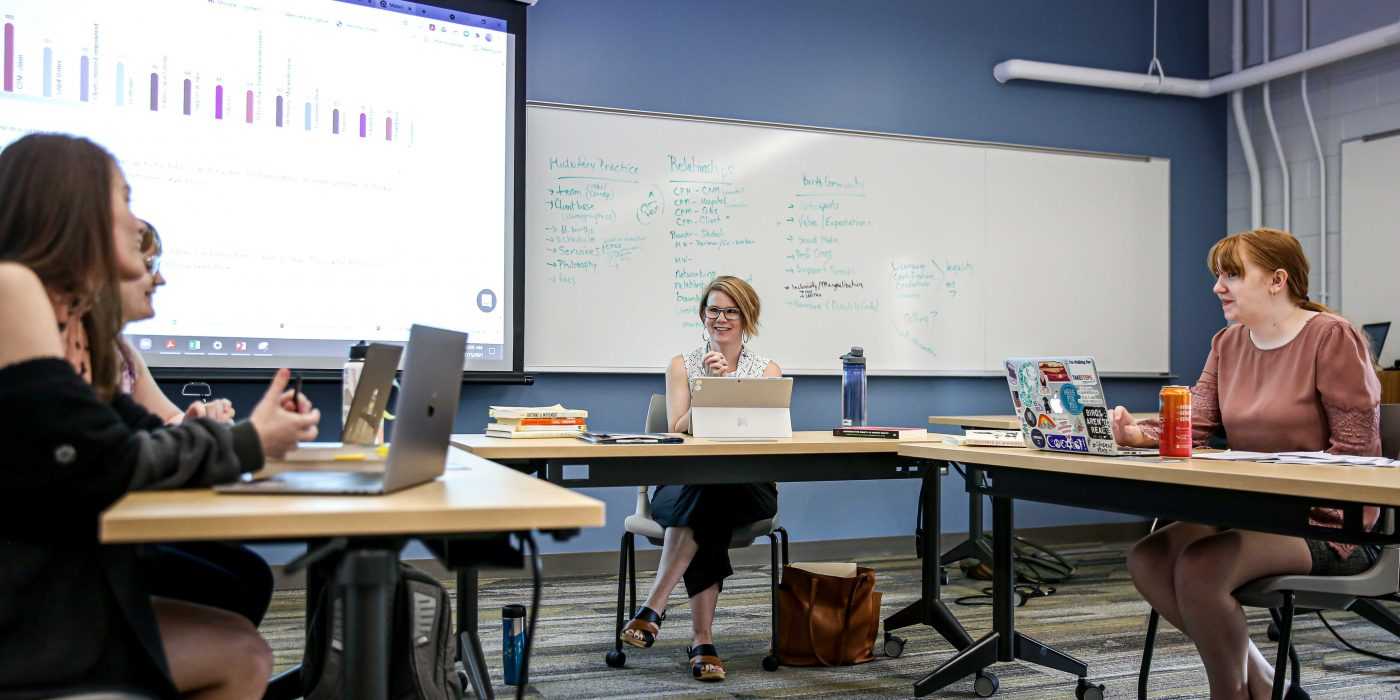 Ringer Distinguished Professor of Sociology Tori Barnes-Brus '97 talks with her students about their research
