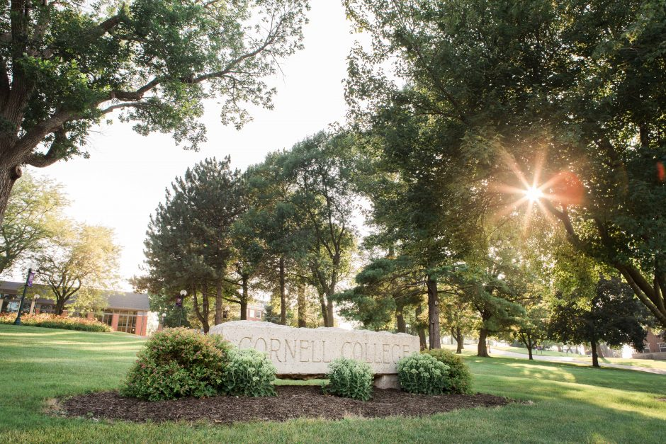 Sun shines through the trees behind the Cornell College sign
