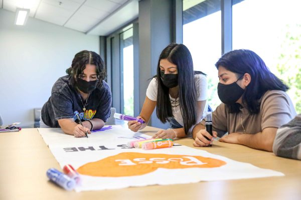 Three students work on a poster using large markers