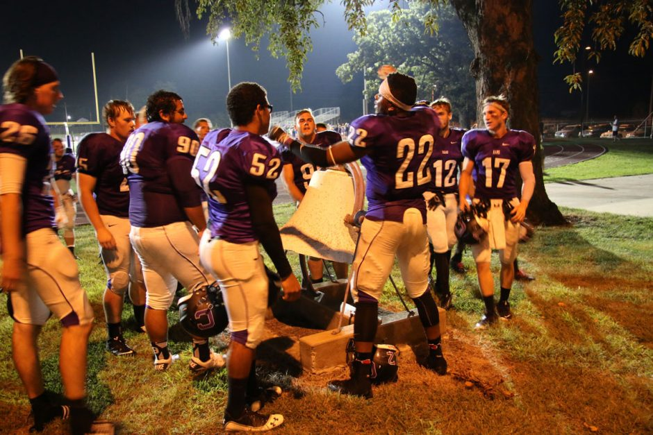 Football players ring the Ash Park victory bell