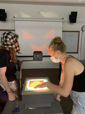 Two students work to create a spooky face on a projector.